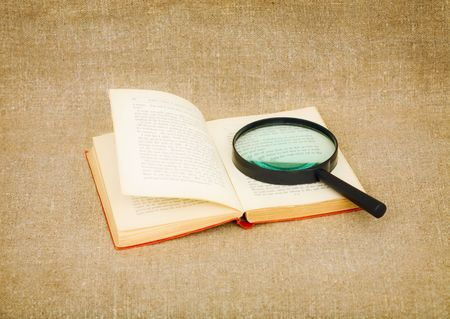 Old book and magnifier glass on canvas background