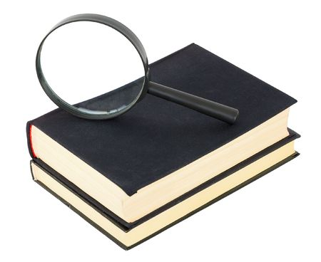 Two black books and magnifier glass on white background photo
