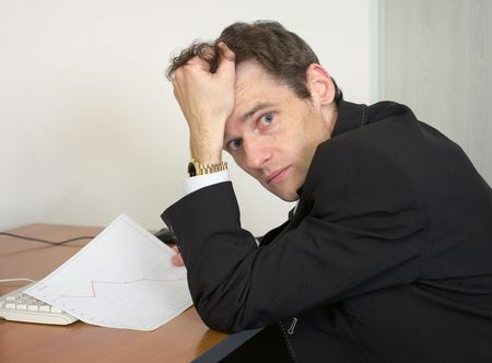 sorrowful: Sorrowful man at the office, on a workplace with graph