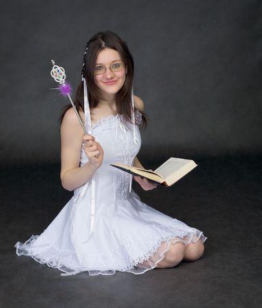 esoterismo: Chica - el mago con el libro sobre un fondo negro Foto de archivo