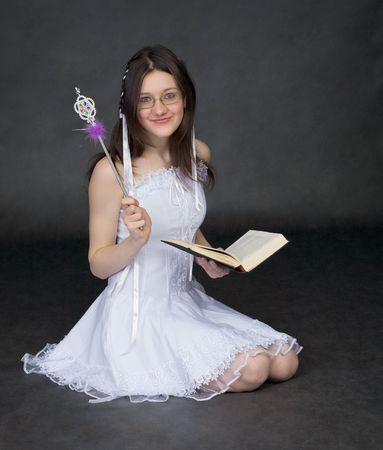 esotericism: Girl - the magician with the book on a black background