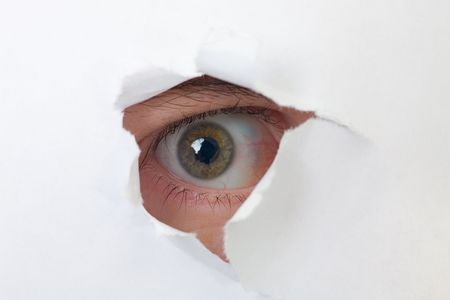 Human eye looking through a hole in white paper Stock Photo - 4838322