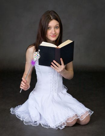 exorcism: Girl in a white dress with the book and a magic wand