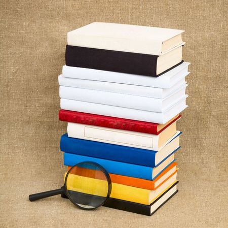 Books and magnifying glass on the fabric background photo