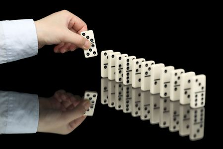Domino bone in hand on the black background photo