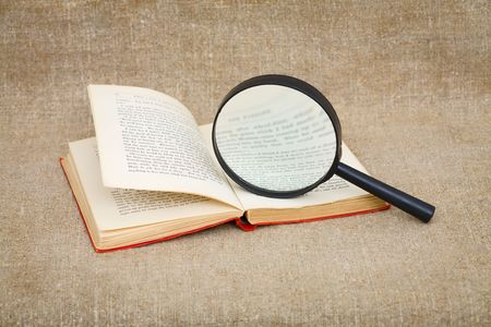 Still-life from a magnifier and the old book photo