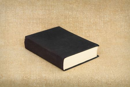 One old big black book on brown canvas background Stock Photo