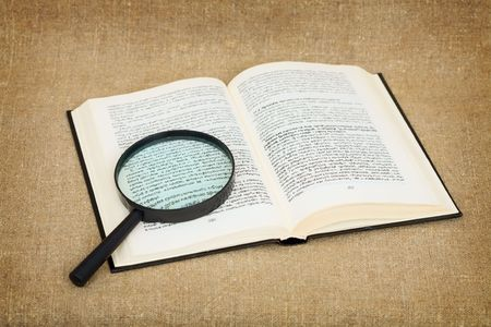 Open book and magnifier on canvas background - a still-life photo