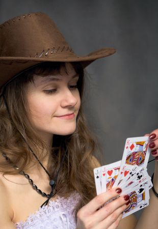 Cowgirl with a playing-cards in hand on black background