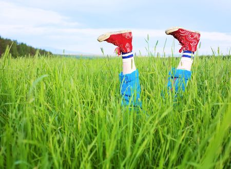 summer shoes: Amusing feet in the red gym shoes, cheerfully sticking out of a grass Stock Photo