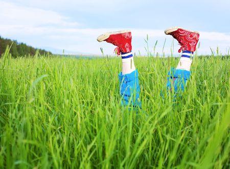 lying in grass: Divertido pies en el gimnasio los zapatos rojos, que salen alegremente de una hierba