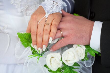 Hands of a newly-married couple with wedding rings against a bunch of flowers Stock Photo - 5173393