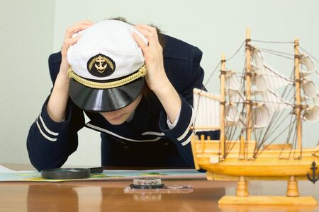 vexation: Depressed girl in a sea uniform over a map Stock Photo