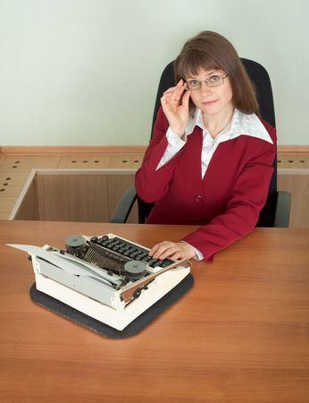 The young girl in office armchair with typewriter photo