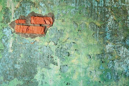 Damaged painted old brick wall with hole photo