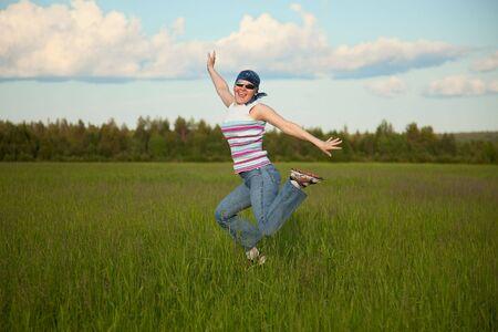 bandana girl: The girl in bandana jumping on a green field Stock Photo