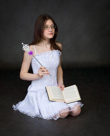 esoterismo: Chica - el mago con el libro se asienta sobre un fondo negro Foto de archivo