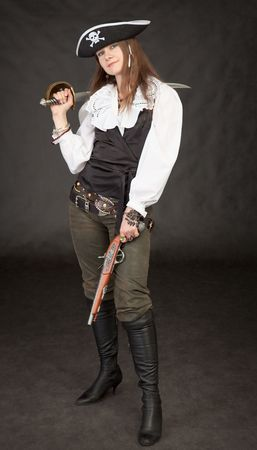 Beautiful girl - pirate with sabre and pistol on a black background photo