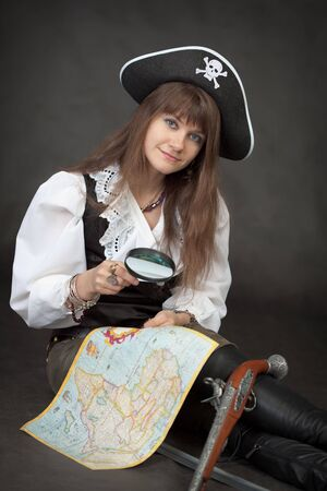 Pirate girl with sea map and pistol sit on a black background photo