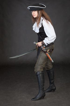 Pirate girl with pistol and saber on black background photo