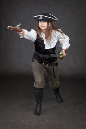 Pirate girl rush to the attack with pistol and sabre photo