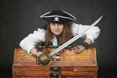 Woman the pirate with a sabre and chest with treasures photo