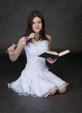 esoterismo: Chica - hadas en un vestido blanco con una varita m�gica y el libro sobre un fondo negro