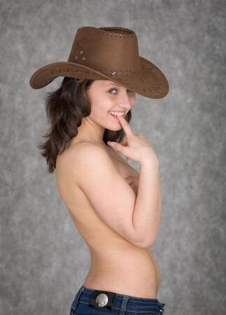 Beautiful playful young woman in a cowboy hat on a grey background photo