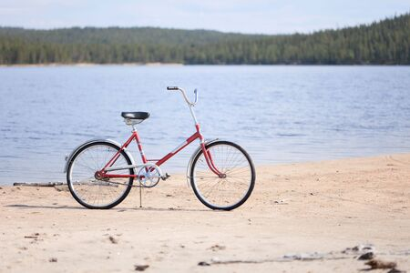 Old red bicycle photographed on a summer beach photo