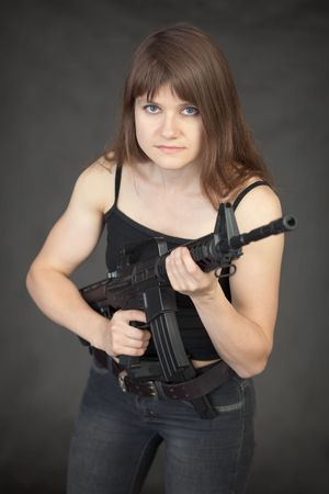 The beautiful young sexual woman - soldier with a rifle in hands Stock Photo - 5615034
