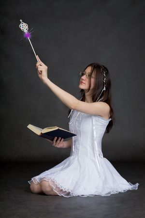 The girl in a suit of the fairy with a magic wand on a black background Stock Photo - 5615044