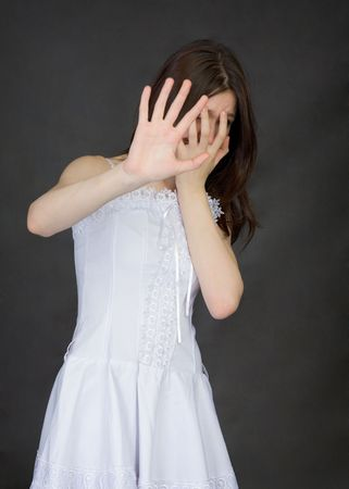 ugliness: The girl cover the face with the hands on a black background