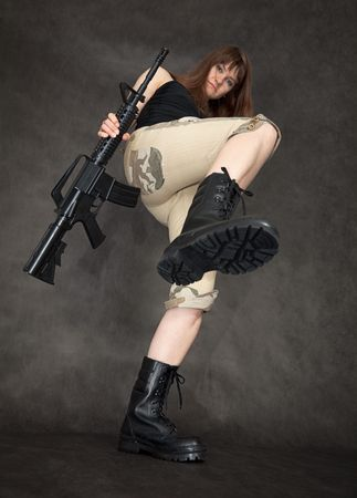 The furious woman with a rifle in hands kicks photo