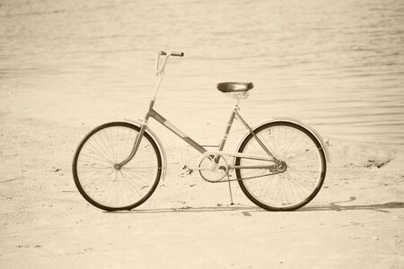 Ancient bicycle photographed on a summer beach - retro sepia photo