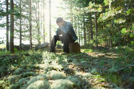 The sad young man sits in wood on a stone photo