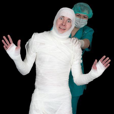 Funny sick in bandage and nurse isolated on black background photo