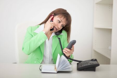 simultaneously: The girl at office talks by several phones simultaneously