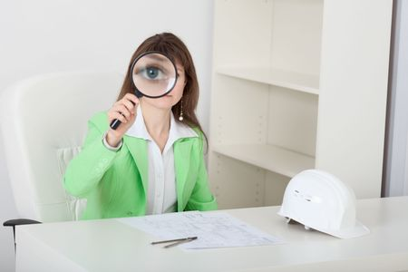 The amusing girl looks at us through the big magnifier photo