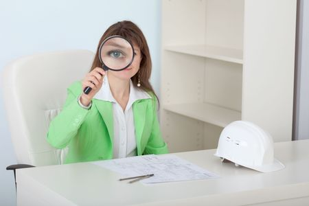 The woman the engineer looks at us through a magnifier with a smile photo
