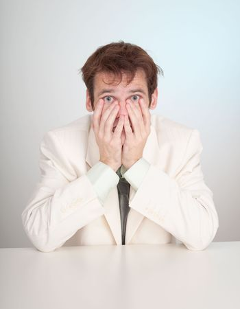 grieved: The young sorrowful people in a white suit sits at a table Stock Photo