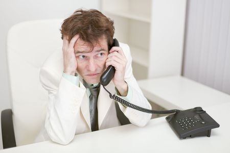 grieved: The frightened guy speaks by phone at office