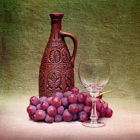 life styles: Still-life with a clay large bottle, a glass and grapes against a canvas