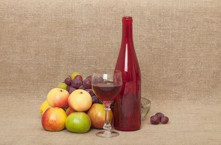 Still-life on a canvas - a red glass large bottle, a glass, apples and grapes photo