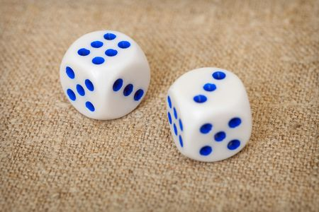 Two playing dices with dark blue points lie on a brown canvas photo