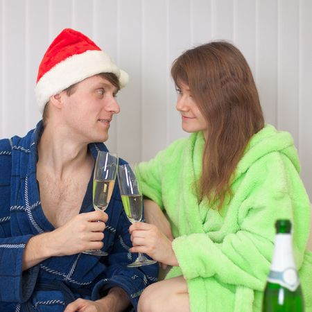 dressing gowns: The young pair drinks champagne sitting on a sofa in dressing gowns