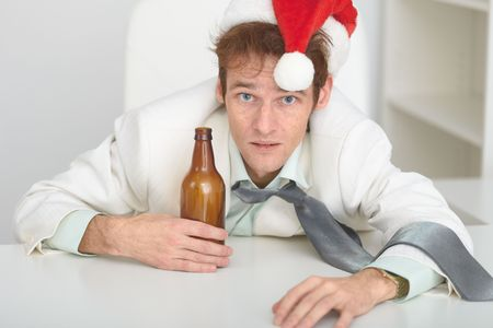 beer and necktie: The young man in a Christmas hat at office with a beer bottle Stock Photo