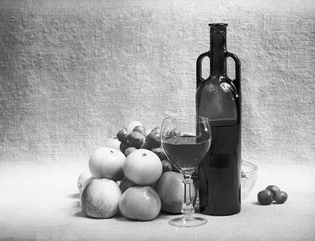 Black and white still-life with wine and fruit on a sacking photo