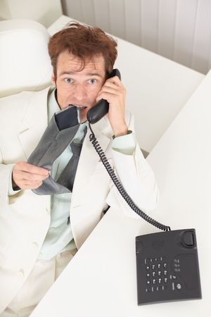 grieved: The young businessman speaks on the phone, worries and bites a tie