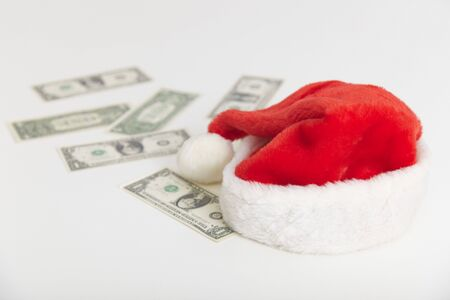 denominations: Christmas cap and some dollars on a white background