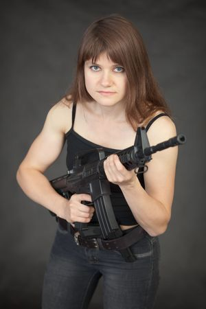 guerrilla: The woman - the fighter of special troops with a rifle in hands against a dark background
